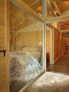 detail-of-interior-glass-wall-with-hand-drawn-etch, Remodelista: Best Bedroom Space, The bedroom has fir paneling and glass walls toward the garden. The interior wall between the bedroom and bath is also a glass wall, with a hand-drawn etched glass patter