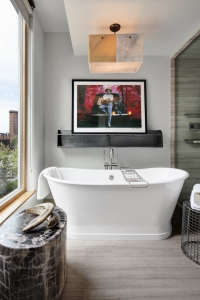A-signed-Hendrix-print-overlooks-the-open-air-tub-, Remodelista: Best Bath Space, This bathroom has an organic modern feel with views overlooking a very urban landscape.