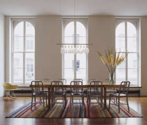 Tribeca-Loft-Dining-Room.-photo-by-Taggart-Sorense, Remodelista: Best Dining Space, In the remnants of an historic barn that had been gutted by fire, the architects re-envisioned the barn's interior.  A single pendant locates the dining room within the mo