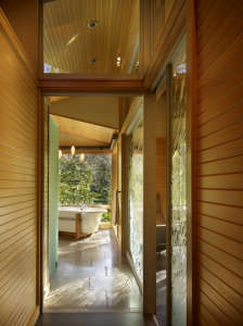 A-glass-wall-with-etched-pattern-separates-bath-fr, Remodelista: Best Kitchen Space, The bath has fir paneling and glass walls toward the garden.  The overall feeling is that of bathing in nature.  Suspended steel mirror frames hang down at the vanity.  F