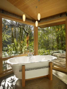 The-tub-is-placed-at-a-glass-corner,-with-views-to, Remodelista: Best Kitchen Space, The bath has fir paneling and glass walls toward the garden.  The overall feeling is that of bathing in nature.  Suspended steel mirror frames hang down at the vanity.  F