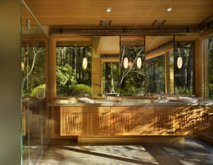The-vanity-is-placed-against-a-glass-wall,-with-su, Remodelista: Best Kitchen Space, The bath has fir paneling and glass walls toward the garden.  The overall feeling is that of bathing in nature.  Suspended steel mirror frames hang down at the vanity.  F