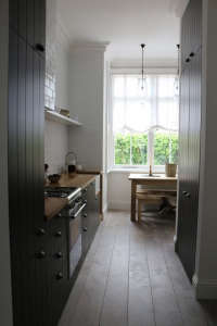 Small-kitchen,-dining-and-living-room-all-in-one., Remodelista: Best Kitchen Space, A very small kitchen space using simple, clean lines. Dark paint, wood and white.