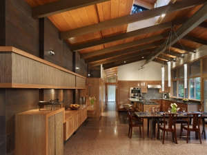 the-dining-space-is-flanked-by-a-weathered-steel-w, Remodelista: Best Dining Space, Dining space is open to the kitchen and separated from the living  by a stone fireplace.  Original terrazzo floor was re-finished.  A new weathered steel wall with suspend