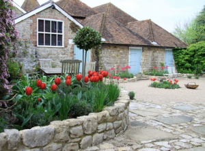 British Garden Cottage House with Blue Doors and Red Tulips, Gardenista