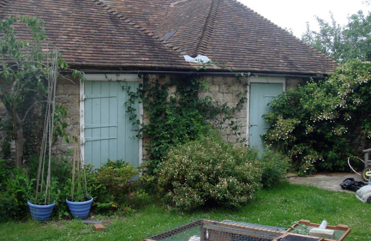 Marian Boswall Before Photo of Cottage in United Kingdom with Too Many Plants and Bushes Against the House, Gardenista