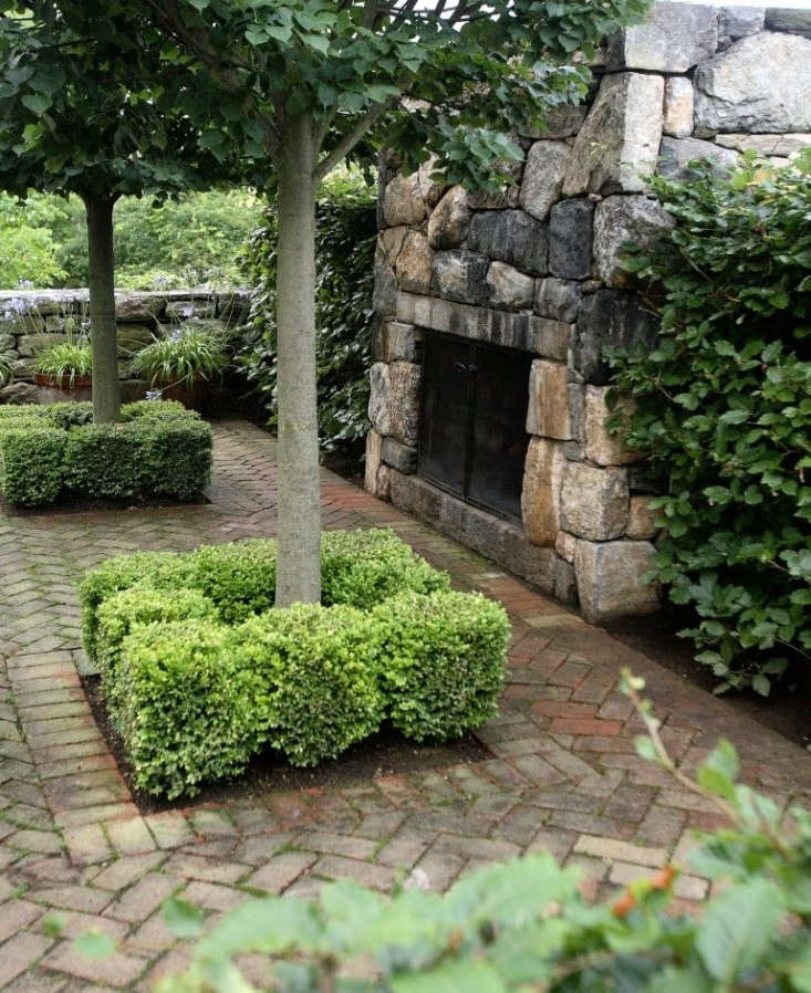 brick-patio-stone-fireplace-boxwoods