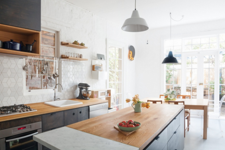 In this kitchen by Melbourne interior architecture firm Hearth Studio, a kitchen island is segmented into American oak and Carrara marble for a work surface.