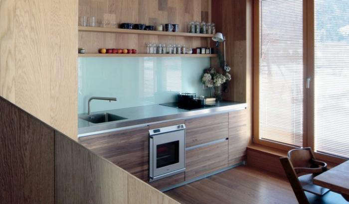 Minimal modern wood kitchen in winter cabin hut in Slovenia with open shelving and modern colors