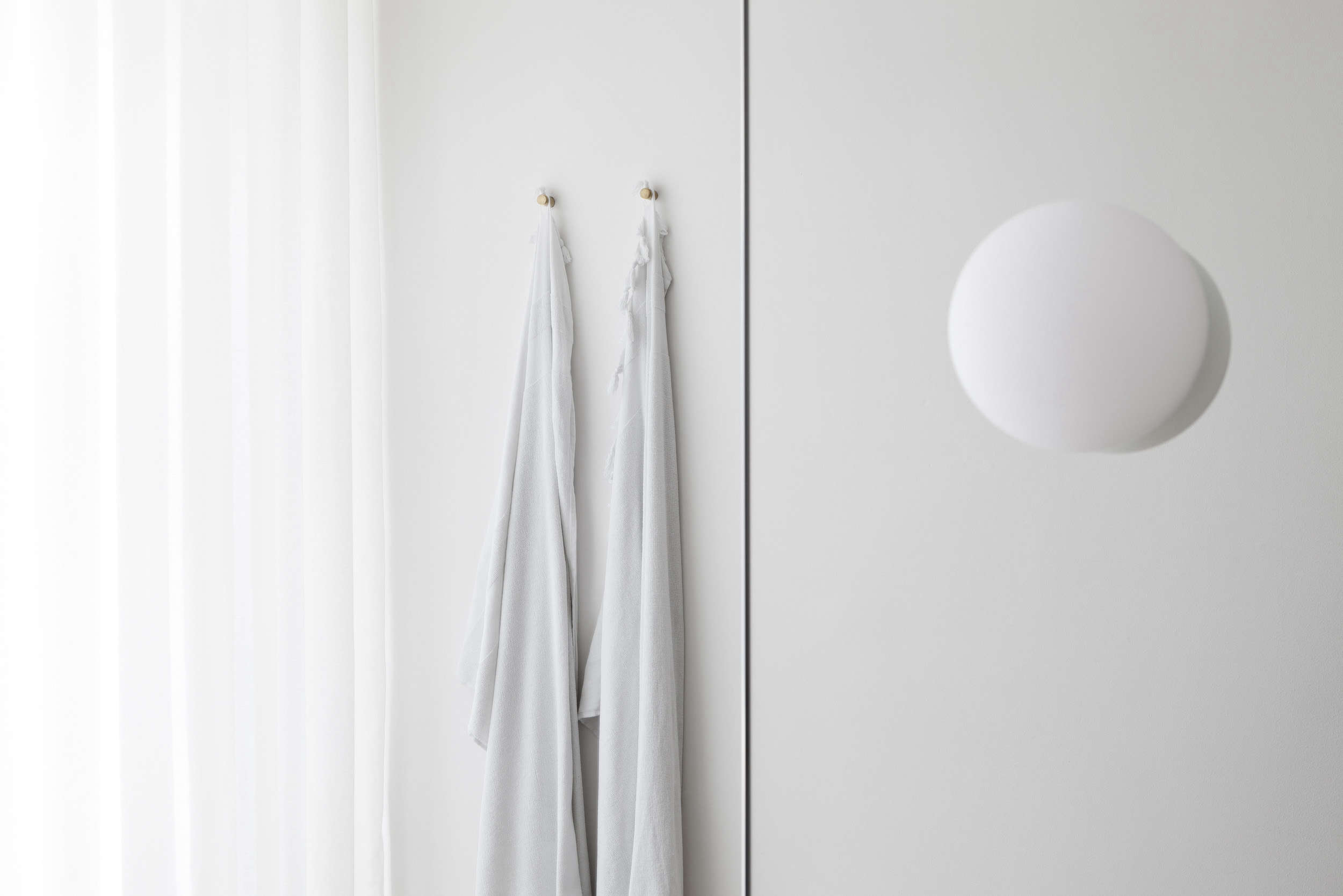 Bathroom hooks in a luxe-minimalist apartment remodel by Studio Oink in Mainz, Germany | Remodelista