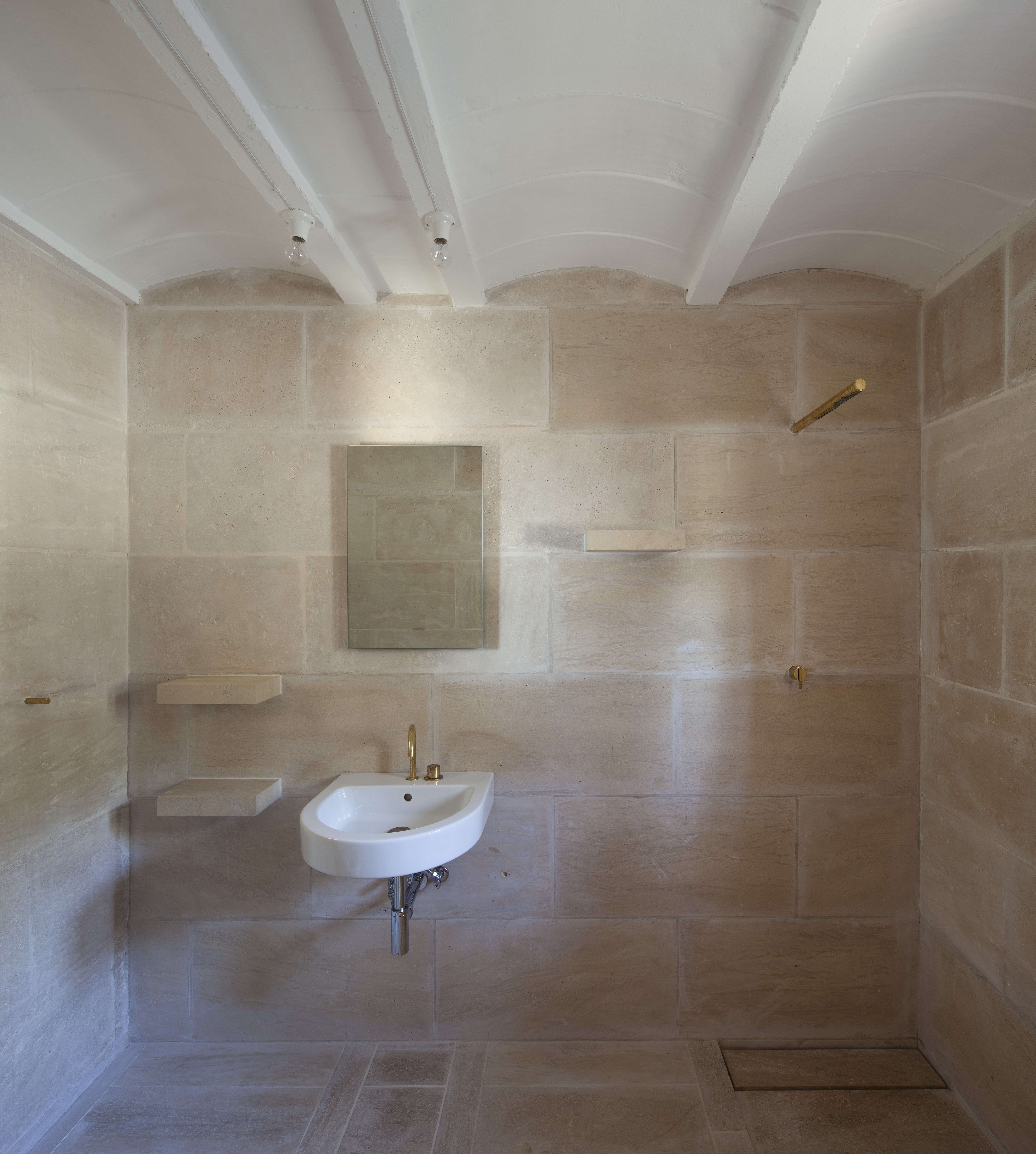 The bare bones bath features almost invisible shower fixtures and integrated stone shelving.