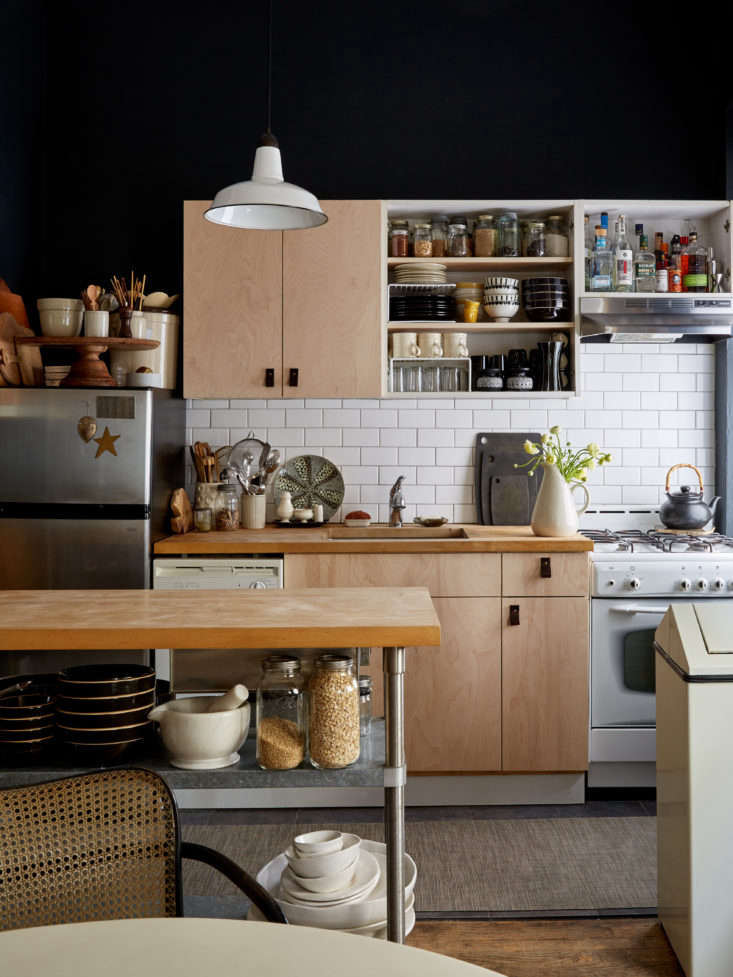 The couple in this New York apartment took their double cabinet doors off of one unit. Fortunately, the cabinet boxes are frameless—no framework or center panel divides the cabinet space. SeeSmall-Space Solutions: 17 Affordable Tips from a NYC Creative Couple for a full look.