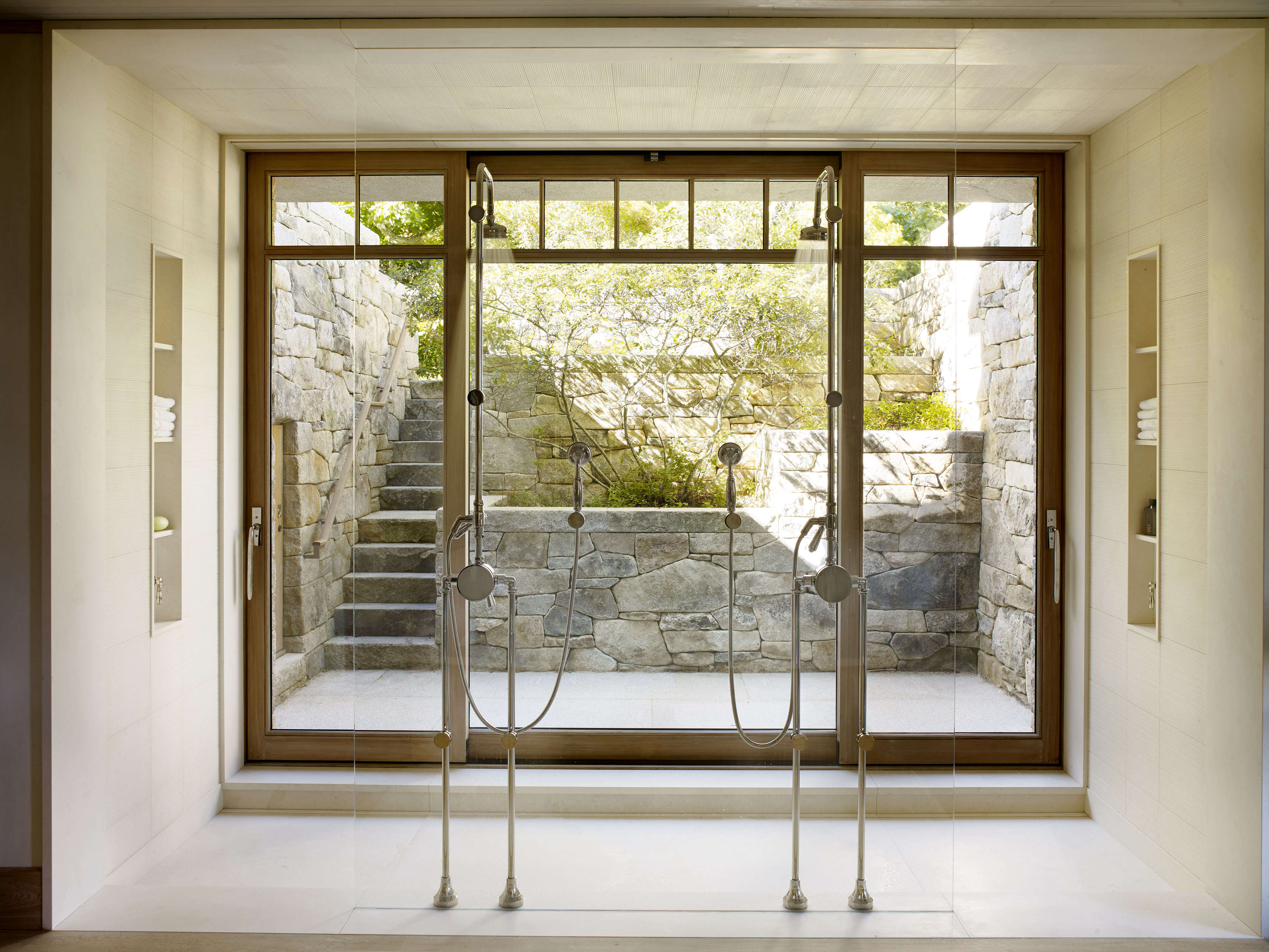 expert advice how to create the perfect bath from the grande shower opens onto backyard greenery light open