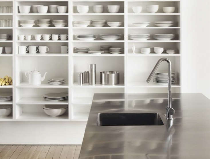 Sleek stainless countersadd industrial style to minimalist built-in shelving inStrategic Storage in a Minimalist Loft.