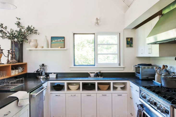 """Julie's horseshoe kitchenin Mill Valley, California, is small but efficient. """"Dinnertime drop-ins are a frequent occurrence, and I love to cook, so it was important to me that the kitchen be outfitted for action,"""" she says. Her architect, Jerome Buttrick, provided well-designed storage that allows for all of the necessities to be kept on hand but out of sight. Inset open-shelving creates an eye-catching mixing bowl display. For a full tour and dissection of the kitchen, see theRemodelista book.Photograph by Matthew Williamsfor Remodelista."""