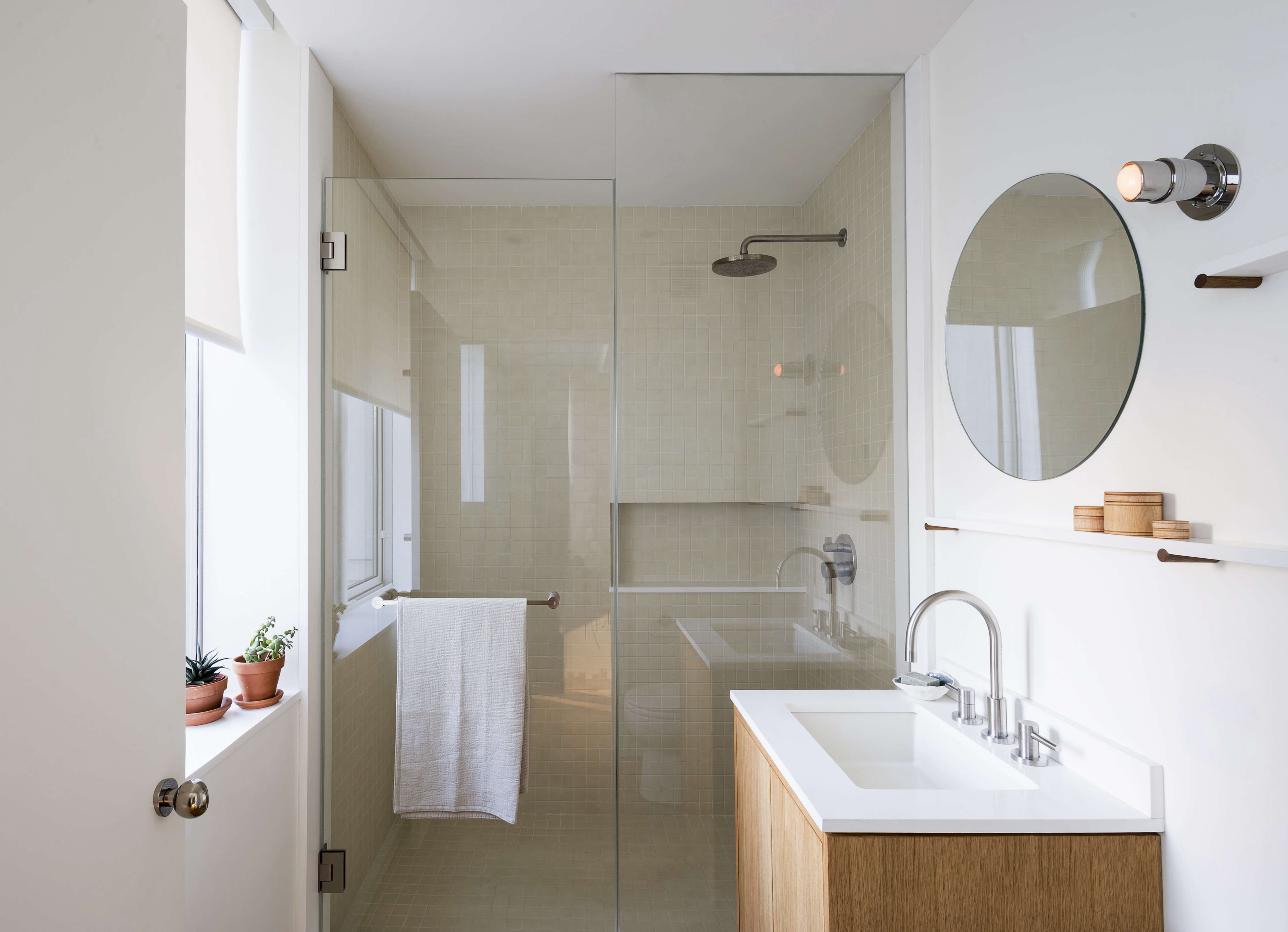 NY apartment small bathroom remodel glass shower and Eileen Gray Pailla wall lamp
