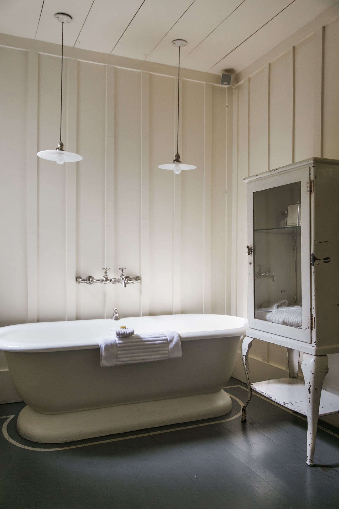 The paneled bath with vintage fixtures and furniture.