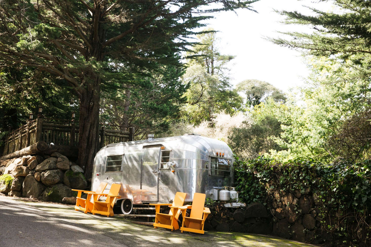 An Airstream trailer and orange lounge chairs marks the entrance to the Manka