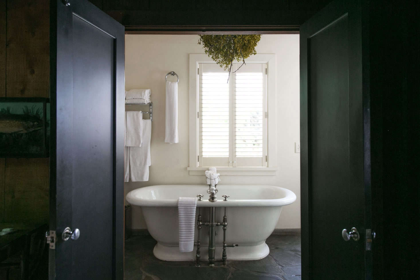 A ball of foraged mistletoe hangs above the freestanding tub in the cabin