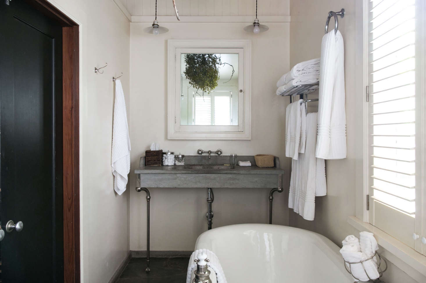 The simple bath with vintage fixtures and a concrete sink.