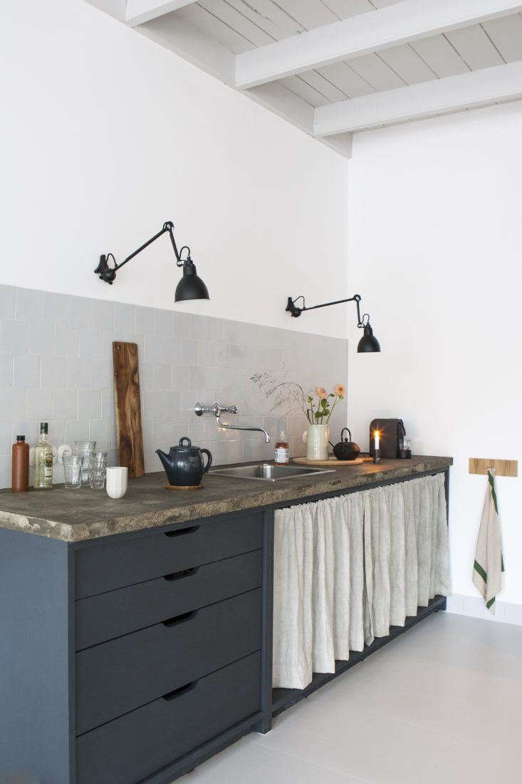 A DIY under-counter curtainsoftens the otherwise hard-edged space. SeeSteal This Look: A Rustic Modern Kitchen in the Netherlands. Photograph byAnna de Leeuw, courtesy ofJan de Jong Interieur.