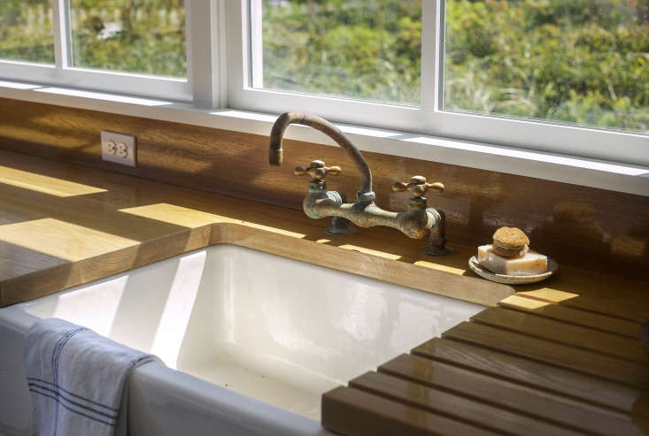 A deck-mounted utility Chicago faucet was stripped down to reveal the brass construction and paired with a ceramic farmhouse sink. (A similar sink is Shaw's 30-Inch Original 3018 Fireclay Apron-Front Sink from Rohl. For more, see our post10 Easy Pieces: White Kitchen Farmhouse Sinks.)
