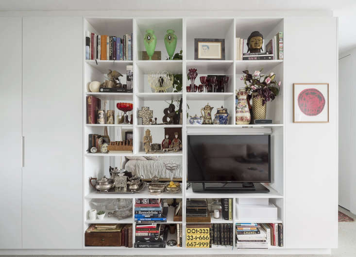 Another instance of shelves as divider. Here, they create a separate bedroom in a tiny studio apartment—and provide ample space for displaying the tenant&#8