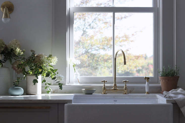 A farmhouse sink and Barber Wilsons unlacquered brass faucet in Jersey Ice Cream Co's house redesign in Rockport, Maine.