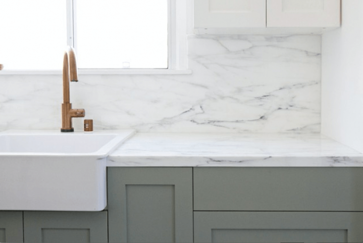 """When designing her kitchen, LA-based designer and blogger Sarah Sherman Samuel ofSmitten Studioexpected to go for Carrara, but discovered """"Carrara is generally more gray with smaller veins, and Calacatta is whiter with more dramatic veins. The slab I found was very white and the veins have the prettiest range of colors, including touches of gold and green."""" Shown here is the finished product with Calacatta counters and backsplash. See more atSemiHandmade Kitchen with Ikea Cabinets."""