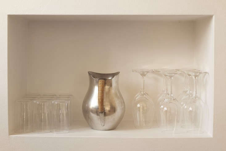 An antique Pewter Pitcher by Just Andersen is stored with glassware in an alcove shelf.