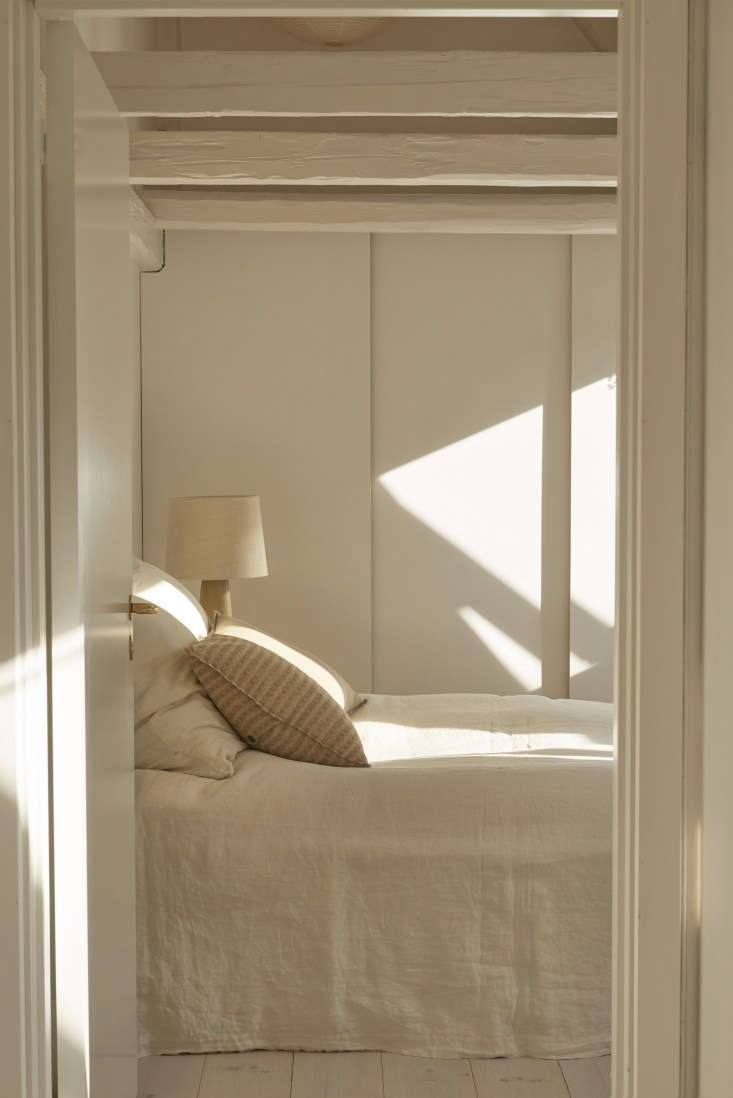 Beautiful natural light in a minimal bedroom with linen by Caroline Feiffer in Copenhagen Photo by Katrine Rohrberg