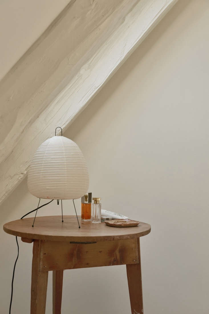A Noguchi Akari 1A Table Lamp and toiletries on a vintage side table.