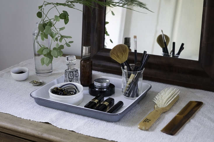 On her dresser, Justine corrals an array of beauty essentials on the tray, with cosmetic brushes in a lab beaker.
