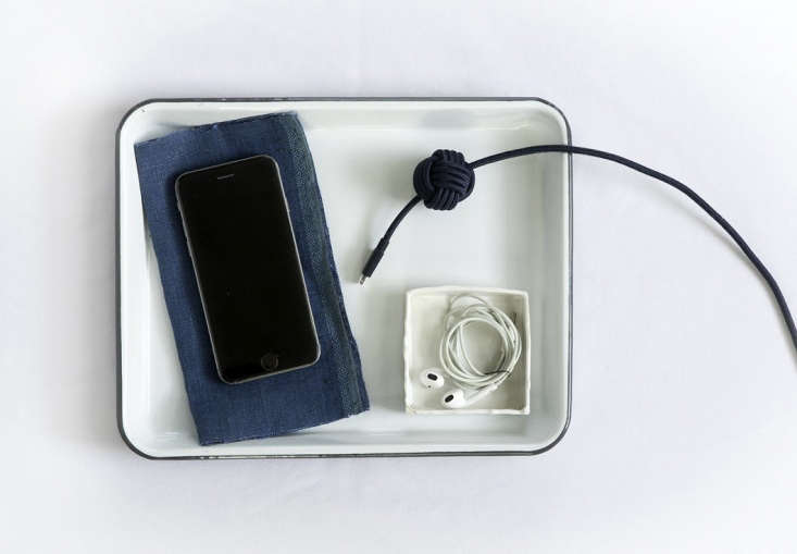 On her desk, Justine uses the tray as a platform for phone charging (note her earbuds tucked tidily in a tiny box).