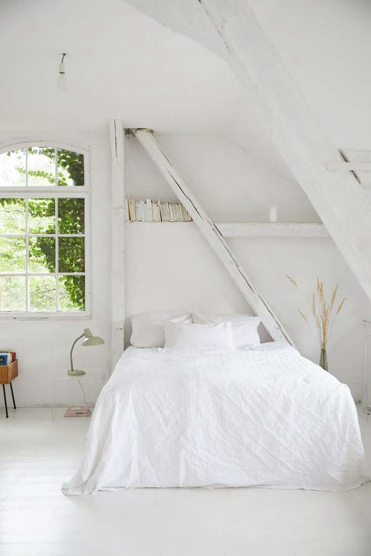 the all white main bedroom is tucked under the rafters. 19
