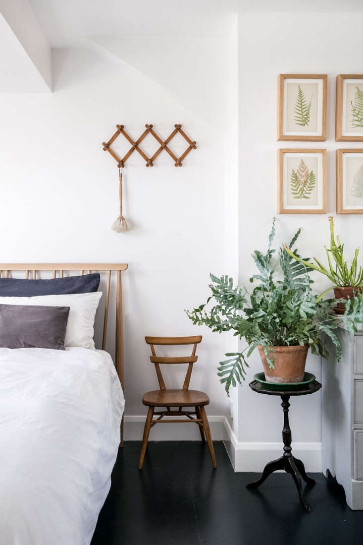 In the bedroom, an exuberant houseplant mingles with a carnivorous cousin. Above the bed is an accordion peg rack; source something similar in Five Favorites: The Useful—and Inexpensive—Accordion Peg Rack.