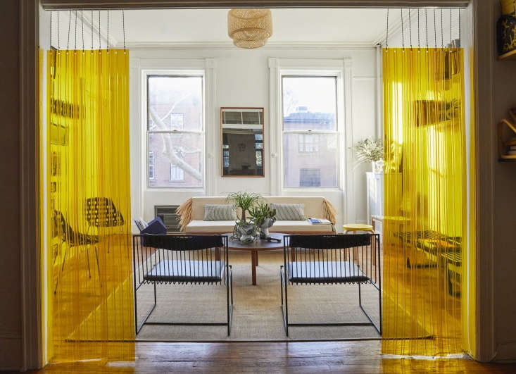 In his New York apartment, designer C. S. Valentin opted for yellowstrip curtains(like the ones used in industrial food storage facilities), hung from a hospital drop chain, to create a bright and semi-transparent divider between living room and home office. Photograph by Jonathan Hökklo, fromAt Home with C. S. Valentin: French Eclecticism in Cobble Hill, Brooklyn.