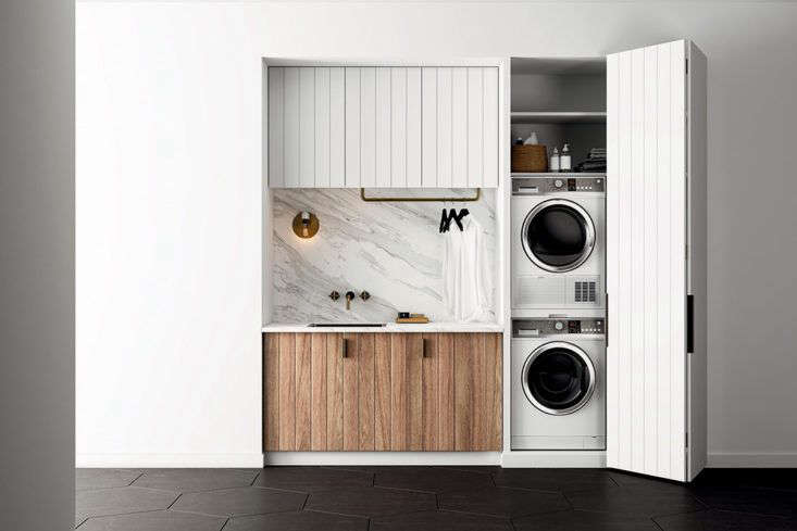 A stacked washer and dryer and storage shelves are concealed behind a paneled bi-fold door. Photograph courtesy ofFisher & Paykel, fromA Marble-and-Brass Laundry Room in Small, Medium, and Large.