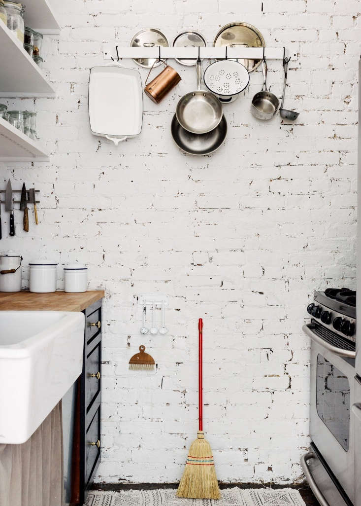 In a tiny kitchen, a sink skirt creates another storage area to conceal cooking tools. SeeA Modern Fairy Tale Told in 800 Square Feet: Sandeep Salter's Family Apartment. Photograph by Jonathan Pilkington for Remodelista.