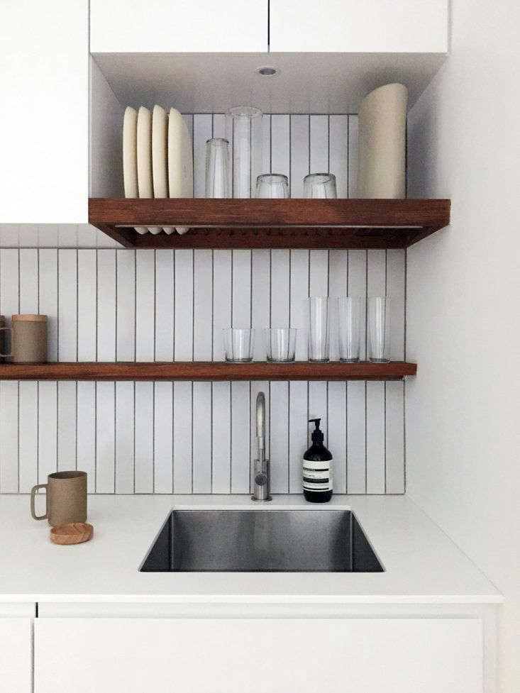 """Above the stainless steel sink is a custom,oiled teak dish rack: """"The dishes dry and live in the same spot, so the counter is never cluttered with a drying rack,"""" said Lee.The backsplash tile is from Heath Ceramics."""