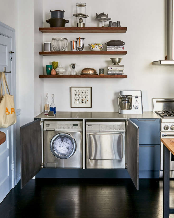 """""""The washer and dryer are Miele; I had to have our carpenter hack the cabinets so they would fit,"""" says Amy Lindburg of her washer and dryer, which live in the kitchen of her San Francisco home.When not in use, they disappear behind cabinet doors. Photograph byDaniel Dentfor Remodelista, fromKitchen of the Week: A Glamorous Kitchen in San Francisco, Ikea Hacks Included."""