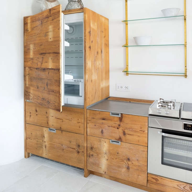 Wood paneled refrigerator in an Italian kitchen made of reclaimed larch wood