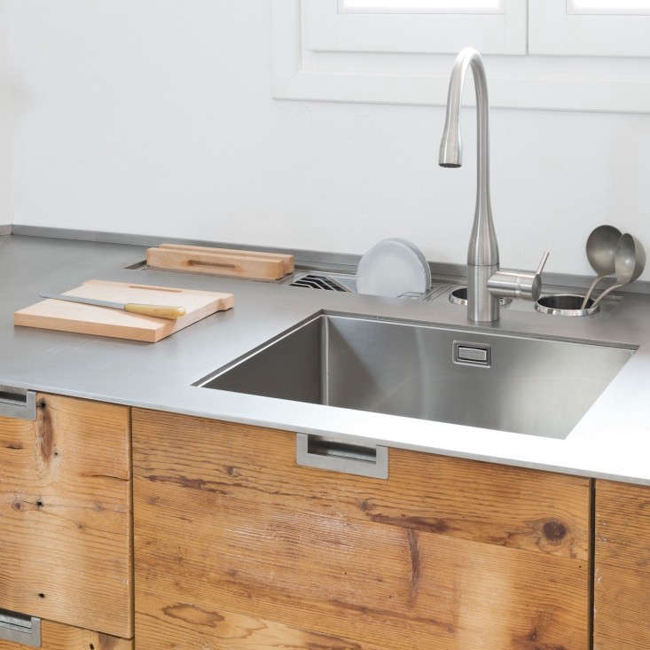 Stainless steel sink in an Italian kitchen made of reclaimed larch wood