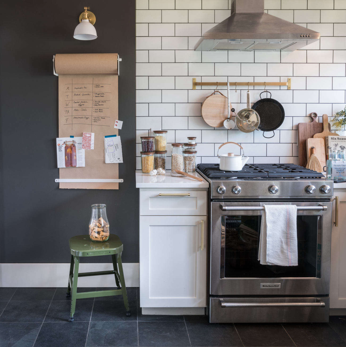 A subway tile kitchen with aWall-Mounted Paper Holder and brass Utility Railfrom Schoolhouse.