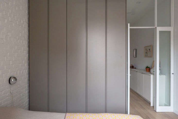 A wardrobe alongside the bed looks sleek when closed. Without so much as door pulls, it looks more like a wall than something to be opened.