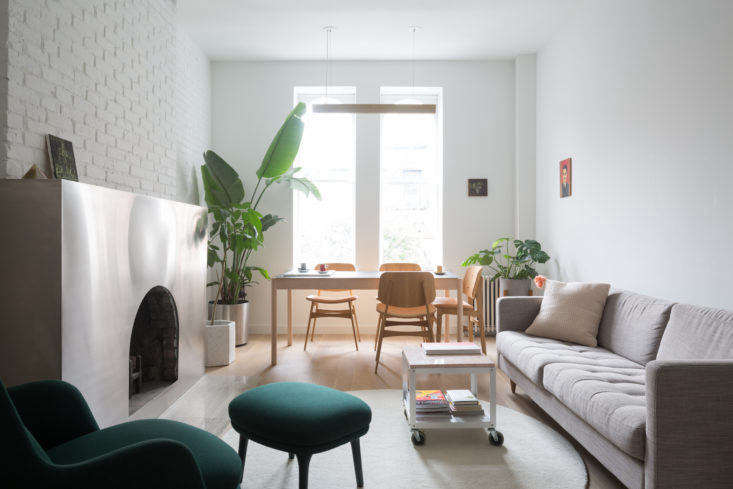 The front living area, after, is white-washed and bright, with minimal furnishings that emphasize the height of the ceilings. A coffee table on wheels allows for flexibility in the small space.