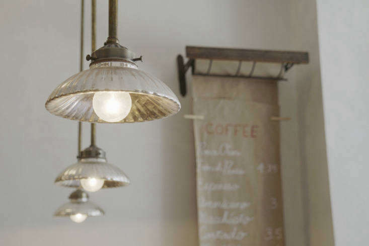 "Above the bar are a row of ""early 1900s mercury light shades from the Czech Republic,"" Kanayama says. We love this look; for a do-it-yourself option, see DIY: Vintage-Looking Mercury Glass Pendant Lights for $25."