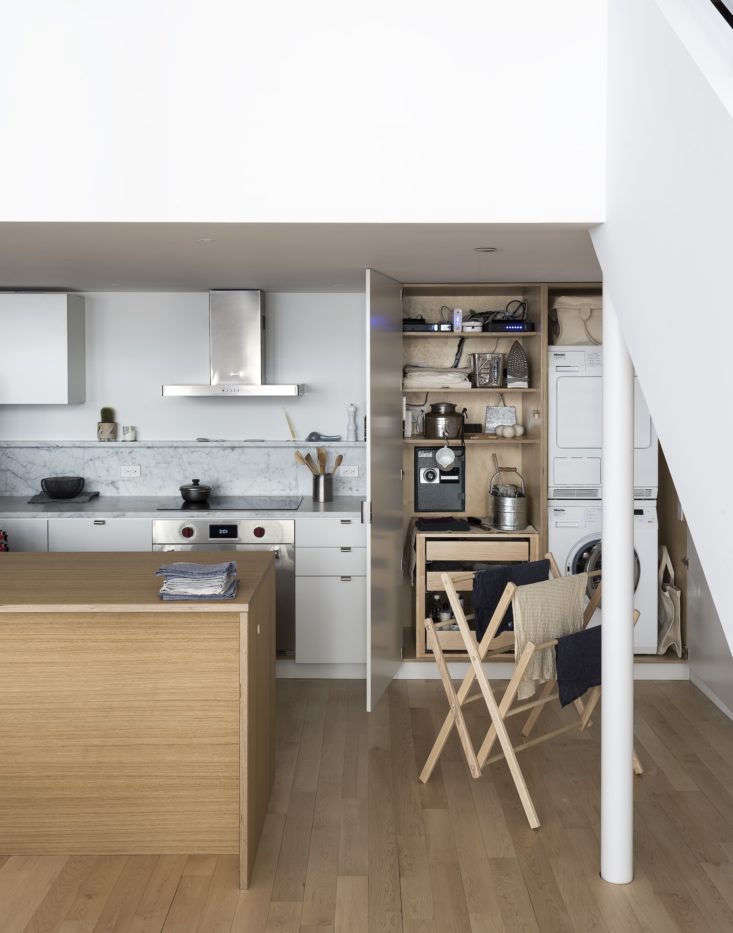 Architect Solveig Fernlund hid a compact and hardworking laundry setup behind floor-to-ceiling doors. Photograph by Matthew Williams and styling by Alexa Hotz for Remodelista: The Organized Home.