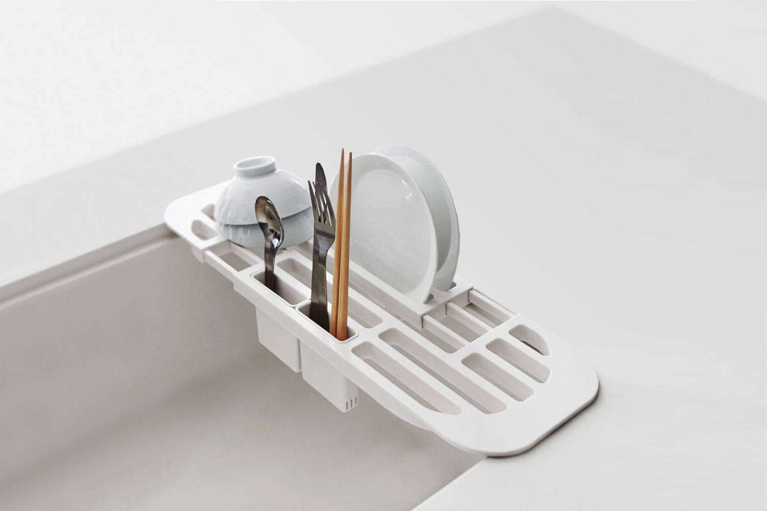 The Yamazaki Tower Sink Drainer fits across the sink (it expands or contracts to fit different sizes) and is made of heavy plastic. It comes with two removable compartments for utensils and the whole thing can be used to rinse vegetables after washing; $35 AUD at Father Rabbit.