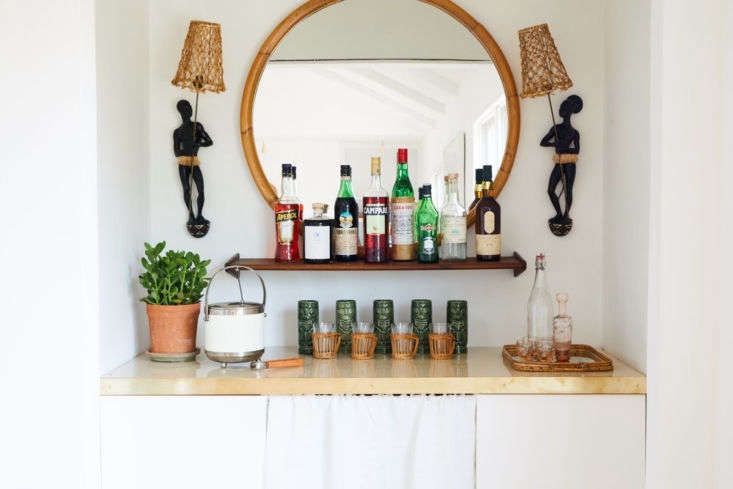 A white curtain panel blends seamlessly into this dining-room bar. SeeVintage Summer: A Seventies-Style Shopable Airbnb in Montauk. Photograph by Nicole Franzen.